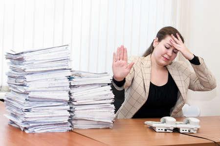 cansancio: Cansado mujer sentada a la mesa en la sala de oficina. Dolor de cabeza y cansancio