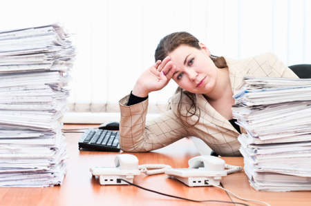 overworked: Tired woman sitting at the table in working place in office room between stacks from paper documents