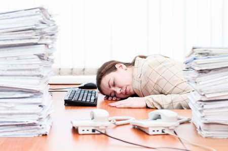 working place: Woman sleeping on working place in office room Stock Photo
