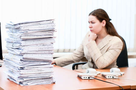 Woman working in office room. Focus on pile of blueprints photo