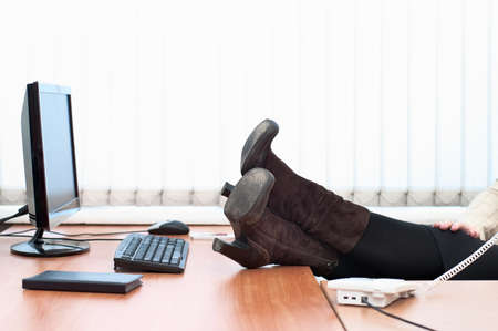 Young caucasian woman in office interior calling by telephone. Legs on a table. Office life photo
