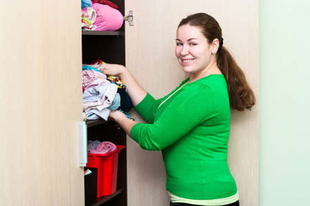 Young caucasian woman holding a suitcase and standing near the wardrobe. Packing things in a shelves. photo