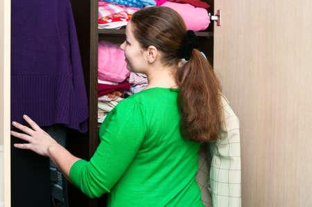 shelfs: Young caucasian woman in the wardrobe packs things on a shelfs.