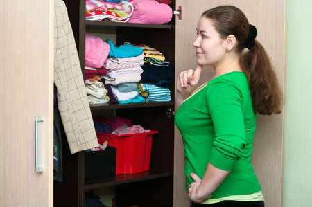 Young caucasian woman thinking about to put on near wardrobe photo