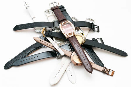 Many female`s wristwatches with leather wristlets on white background photo