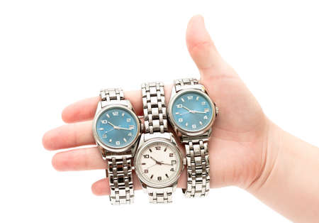 mens: Three wristwatches on women`s hand isolated on white background