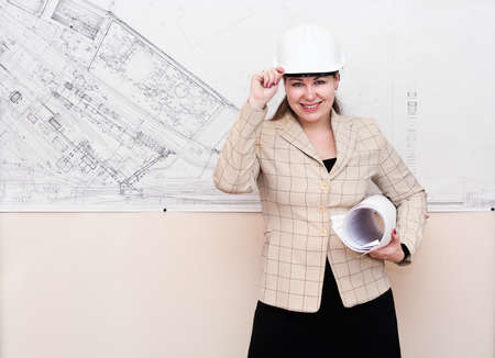 One young woman a architect standin near the big blueprint on wall and showing Stock Photo - 9241593