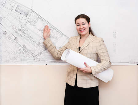 One young woman a architect standin near the big blueprint on wall and showing photo