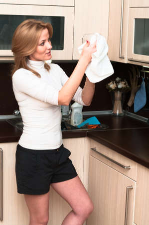 kitchenette: Beautiful happy smiling woman in kitchen interior. One person only