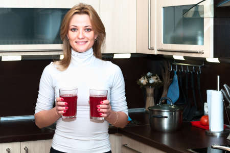 kitchenette: Beautiful happy smiling woman in kitchen interior with drinks Stock Photo