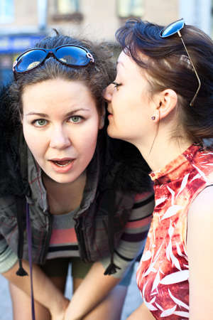 Young beautiful woman whispers something to girlfriend in her ear photo