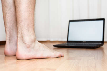 Opened laptop and male feet on the parquet flooring of the room. Laptop not in focus. Focus on legs. photo