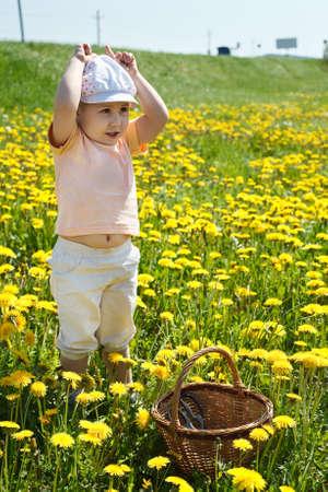 Petit enfant debout sur le champ de fleurs avec panier et jouant en vache Banque d'images
