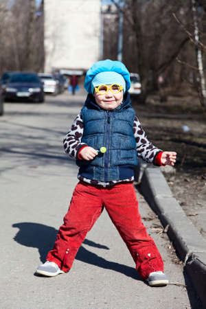 Little child with lollipop is standing outdoors. Funny glasses Stock Photo - 9731404