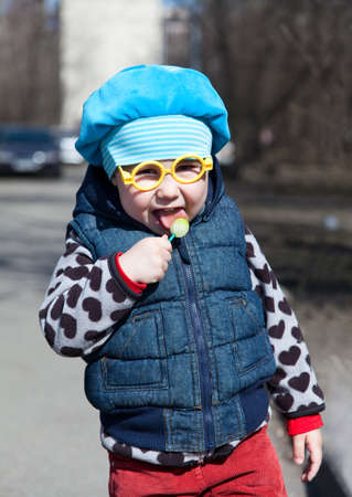 Little child with lollipop is standing outdoors. Funny glasses  photo