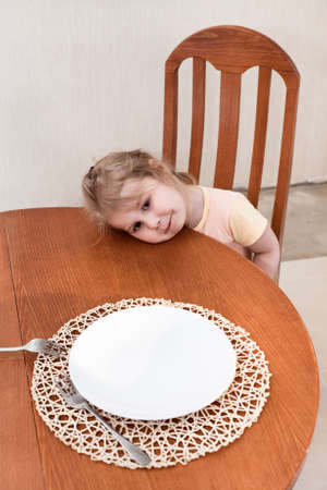 whining: Little child sitting along at table with empty plate Stock Photo