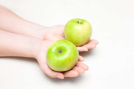 comparison: Two green apples in female hands on white background