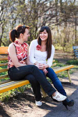 Portrait of two young beautiful women a girlfriends. Sitting and talking together on bench photo