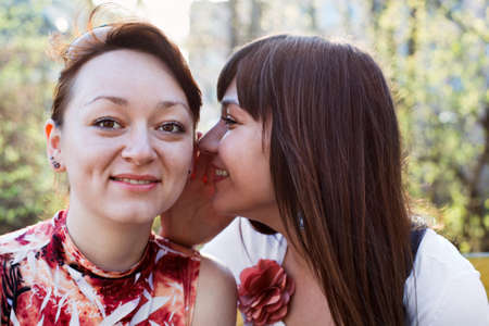 Young beautiful woman whispers something to girlfriend in her ear Stock Photo - 9731403