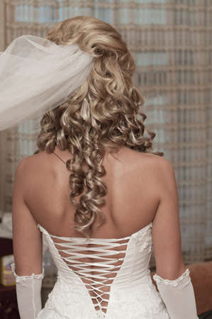 waist up: The back of beautiful young bride with a white corset wedding dress Stock Photo