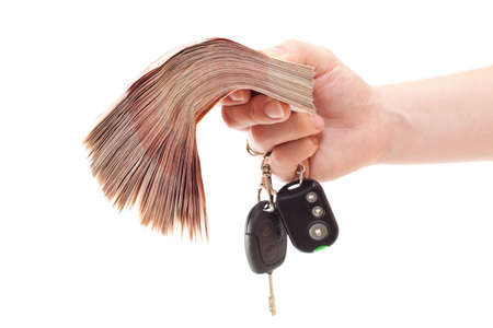 Human hand with bundle of money and automobile keys isolated on white background photo