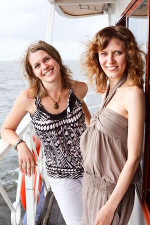 Two beautiful young women a Caucasians standing together on the deck of yacht in cruise  photo