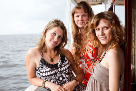 three people only: Three beautiful young women a Caucasians standing together on the deck of yacht in cruise