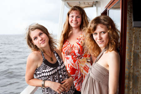 Three beautiful young women a Caucasians standing together on the deck of yacht in cruise  photo