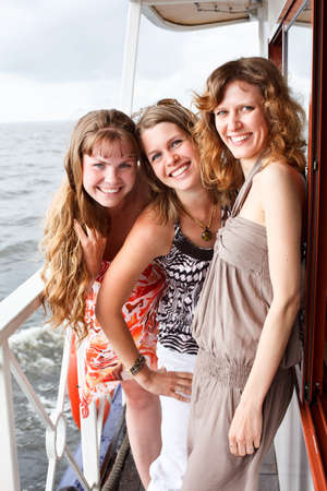 caribbean cruise: Three beautiful young women a Caucasians standing together on the deck of yacht in cruise