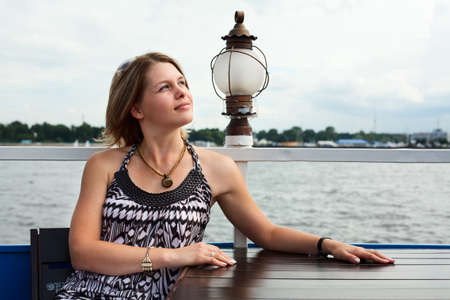 nice day: Beautiful woman sitting along at the table in embankment cafe Stock Photo