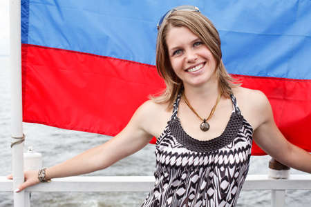 20 25: One Russian beautiful young woman is standing under flag of Russia Stock Photo