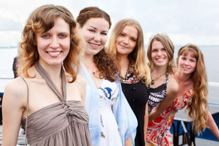 Five young beautiful women are standing in line. Caucasian people. Summer time photo