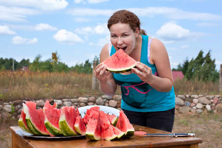 Young woman eating watermelon. Many red slices on table. Outdoors photo