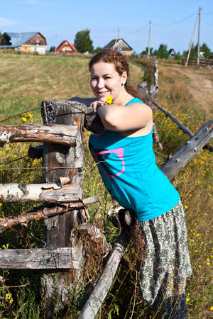 One young Caucasian Russian woman near village fence Stock Photo - 10394303