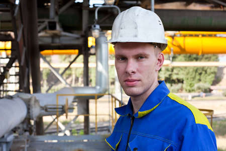 hard look: Young handsome man constructor in white hardhat and blue uniform. Close up portrait
