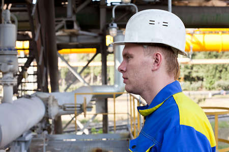 Young handsome man constructor in white hardhat and blue uniform. Close up portrait Stock Photo - 10326534