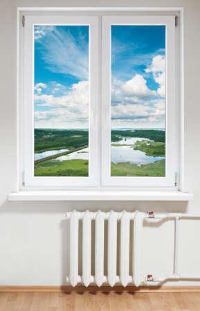 radiador: Ventana de pl�stica blanca con radiador bajo.Ver a trav�s de vidrio Foto de archivo