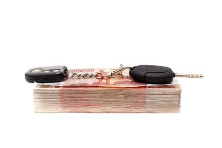 hedging: Car keys on bundle of money isolated on white background
