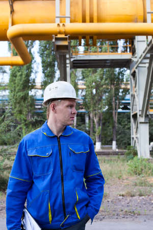 Young handsome man constructor in white hardhat and blue uniform. Stock Photo - 10510491