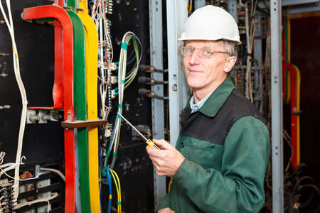 Mature electrician working in hard hat with screwdriver Stock Photo - 10905009