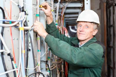 dolgozó: Érett villanyszerelő dolgozik keményen kalap kábelek és vezetékek