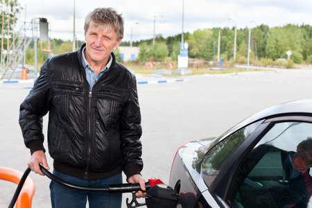 Oudere man het vullen van de moderne auto met benzine in benzinestations