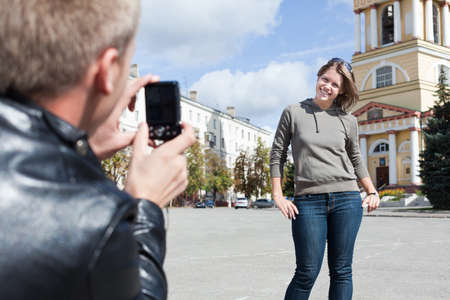 Man photographing young woman against city`s attractions. Summer time, outdoors. Loving couple photo