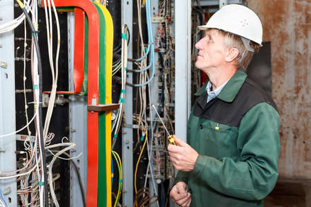 electrical panel: Mature electrician working in hard hat with screwdriver