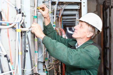 ingenieur electricien: �lectricien d'�ge m�r de travail dans le chapeau dur avec des c�bles et fils Banque d'images