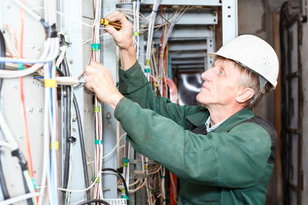 electrical wires: Mature electrician working in hard hat with cables and wires