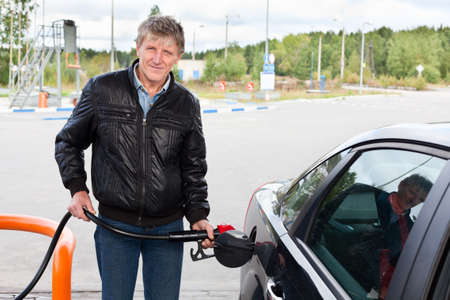 refuel: Mature man filling the modern car with gasoline in gas stations