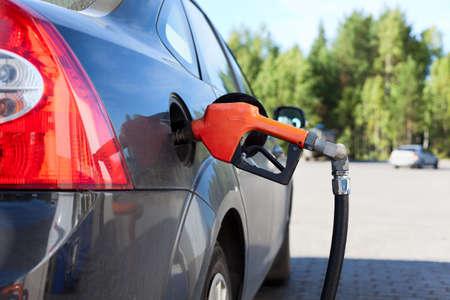 gasolinera: Reabastecimiento de combustible en el coche de la boquilla del tanque negro en la columna de llenado de combustible. Día de verano. Coche negro