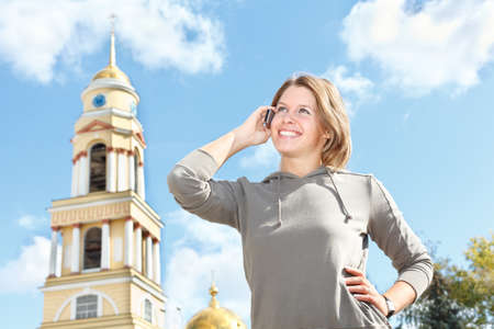 Young Russian beautiful girl calling by mobile phone outdoors. Summer time, sunny day, blue sky. photo