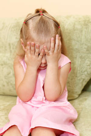 Little child a girl in pink dress sitting on sofa in domestic room and closes face by hands. photo